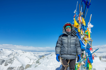 woman climber in helmet and down jacket with trekking sticks stand on top of a mountain