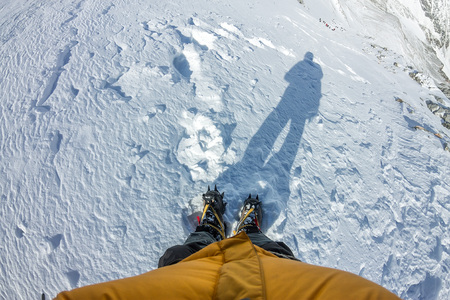 First person view to legs in crampons standing in the snow