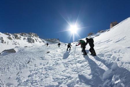 Scalatori legati che scalano montagna con campo di neve legati con una corda con piccozze e caschi