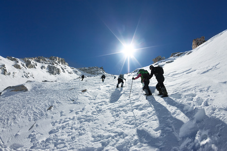 Tied climbers climbing mountain with snow field tied with a rope with ice axes and helmets 스톡 콘텐츠