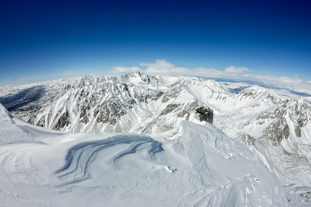 View from the ridge to the top of the snowy mountains to the valley and horizon