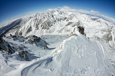 View from the top of the snowy mountains to the valley and horizon