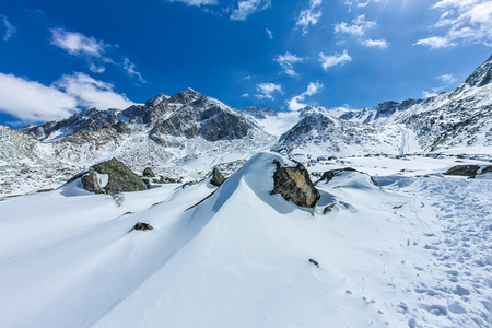 View from the valley to the top of the snowy mountains under the blue sky