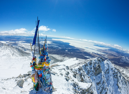 Tibetstkimi post with the flags on the top of a mountain with views of the icy lake Фото со стока