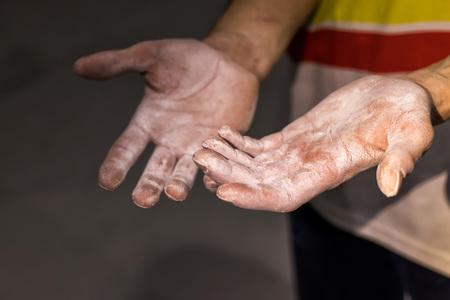 Climber hands lubricates magnesium powder before starting training