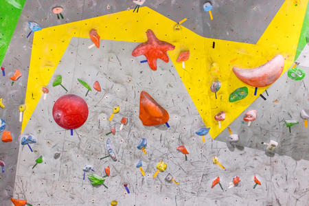 Climbing wall in the boulder hall with colored hooks