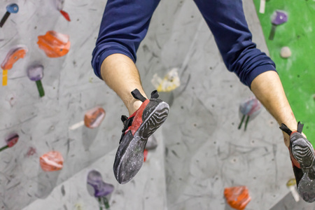 Climbers legs in shoes hang on the wall in a jump