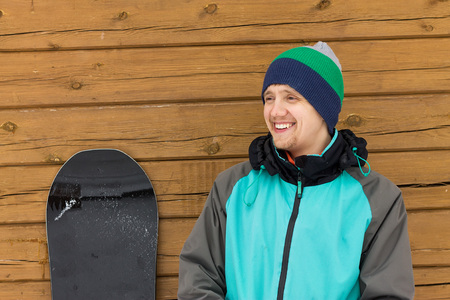portrait man with snowboard and hat and splitboard near wooden wall Фото со стока