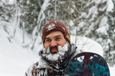 Portrait bearded man ski goggles holding snowboard in the mountains