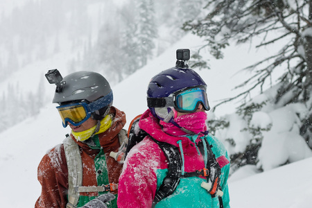 portrait of a couple of snowboarders wearing helmets in the snow looking in different directions