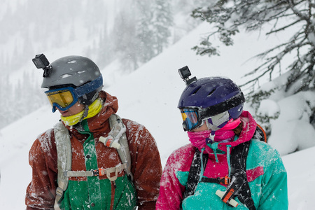portrait of a couple of snowboarders wearing helmets in the snow looking down