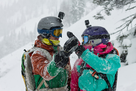 portrait of a pair of snowboarder freeriders wearing helmets in the snow give five