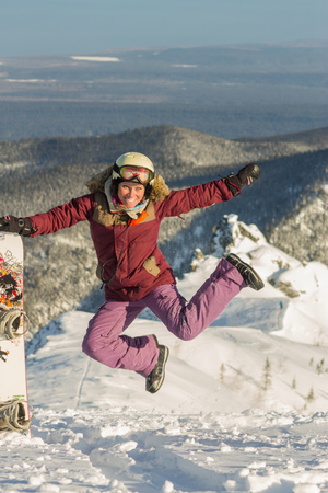 Snowboarder girl freerider is jump in the snowy mountains in winter under the clouds