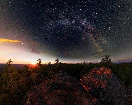 Dawn in the forest under the starry sky a milky way. Panorama Фото со стока