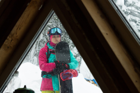 Woman freerider snowboarder standing in a snowy forest, the view from the window