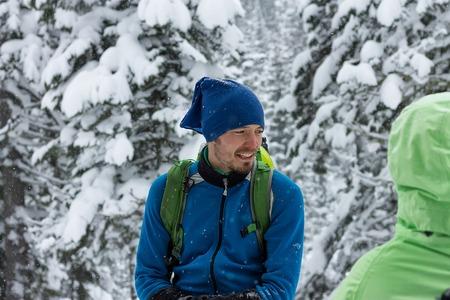 portrait of male freerider in snowfall in winter forest