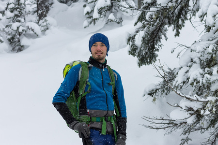 portrait of male freerider in snowfall in winter forest