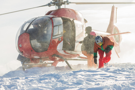 Landing people from a helicopter, freeriders snowboarders on the mountain
