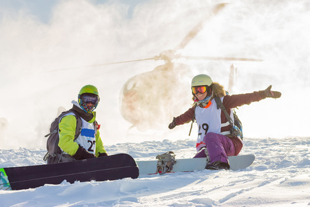 pair of freeriders of snowboarders on background helicopter lands