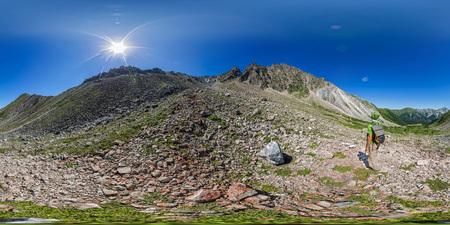 man backpacker stands on top in the mountains. Spherical panorama 360vr
