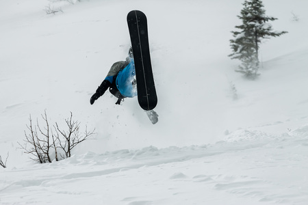 Snowboarder freerider jumping from a snow ramp on a background of forest and mountains Фото со стока