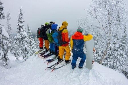 Group team of free-riders skiers, snowboarders stand on the mountainside and look down Фото со стока