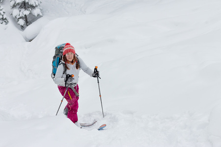 Woman skier freerider skitur uphill in snow in winter forest Фото со стока