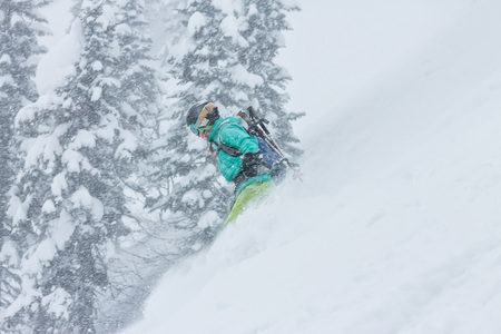 Woman snowboarder freerider goes down on powder snow in the mountains in a snowfall