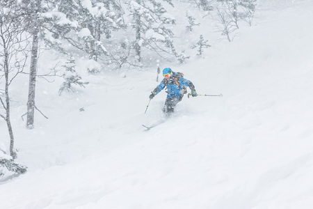 man skier freerider goes down on powder snow in the mountains in a snowfall