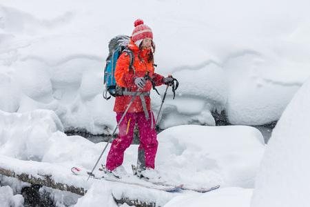 Woman freerider skier crosses the river on logs