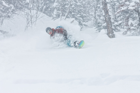 man snowboarder freerider goes down on powder snow in the mountains in a snowfall Фото со стока