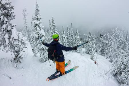 Man splitboard freerider standing at top of ridge. Ski touring in mountains, winter freeride extreme sport Фото со стока