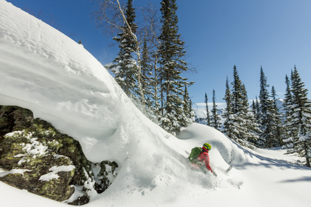 Freerider skier jumps from a rock of snow in trees in the mountains Фото со стока