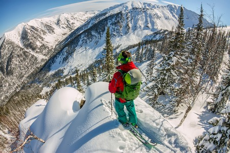 Man standing at top of ridge. Ski touring in mountains. Adventure winter freeride extreme sport Фото со стока