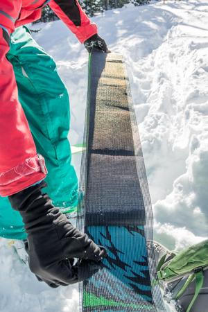 man freerider installs glue camus on skis, in snow wild mountains Фото со стока