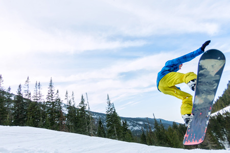 Snowboarder freerider jumping from a snow ramp in the sun on a background of forest and mountains