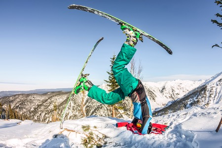 Freerider skier doing yoga stands on his head in skiing in the snowy mountains.