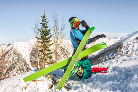 Skier freerider doing yoga skiing in snowy mountains.