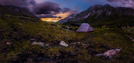 Panorama tent in the mountains on a background of purple clouds at sunset. Фото со стока