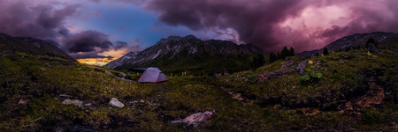 tent in the mountains against the backdrop of purple clouds at sunset. Cylindrical 360 panorama.