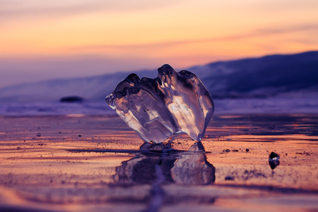 piece of ice on a winter baikal in a purple sunset light.