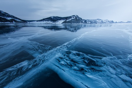 the cross of deep cracks in the thick ice of the winter lake Baikal opposite the rocky mountain of Olkhon Island.