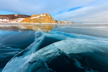 the cross of deep cracks in the thick ice of the winter lake Baikal opposite the rocky mountain of Olkhon Island