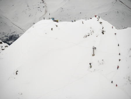 group of freeriders snowboarders skiers rises uphill in the Caucasus in the rose khutor