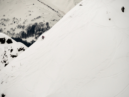 freerider skier descends a steep slope of white snow and trees in the Caucasus Mountains Stok Fotoğraf