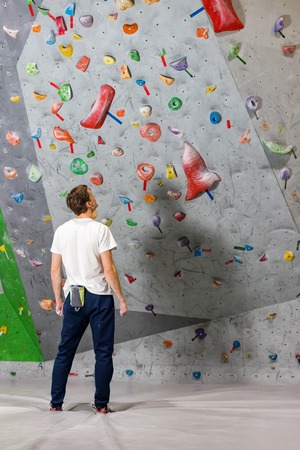 Rock climber stands and looks at the climbing wall with hooks in the boulder hall Фото со стока - 119149921