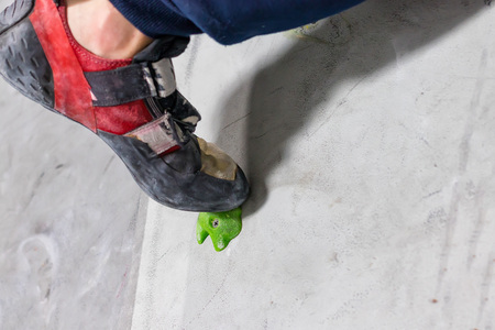 rocky shoe on a tiny, scanty snare stands with the tip of the sock in close-up on the climbing wall in the room