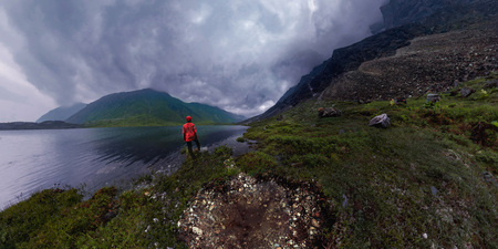 man stands by lake in red jacket in cloudy weather panorama