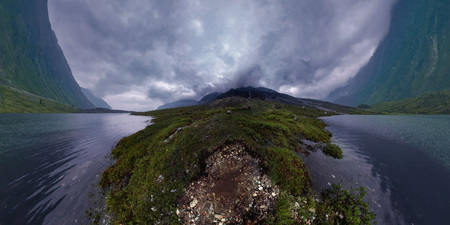 Black mountains in rain clouds, the foot covered with stones and green grass. Wide angle panorama