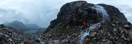 man in red stands under a waterfall on a black rock in the mountains on a cloudy rainy day. 360 cylindrical panorama